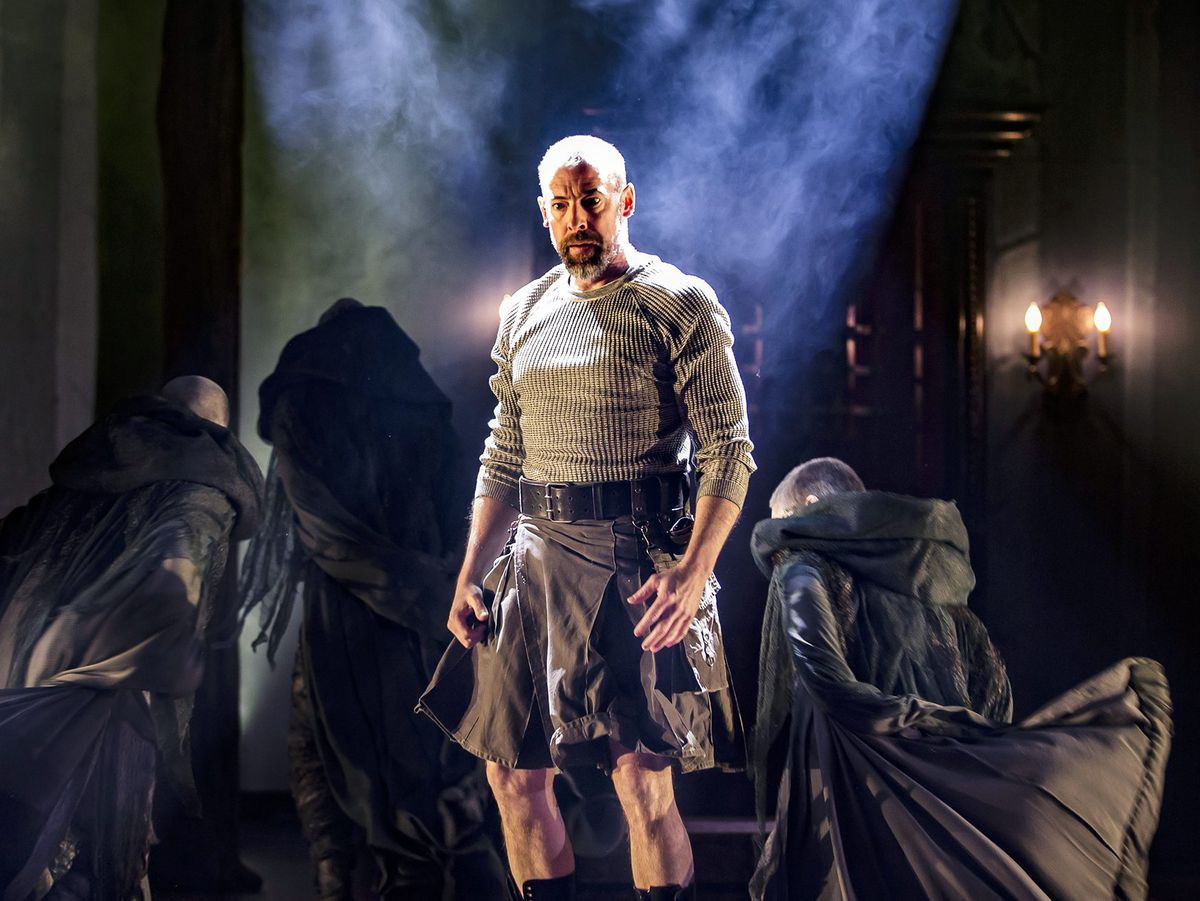 """Macbeth (Ian Merrill Peakes) weighs the cost of his ambition, shadowed by the spirits of the Weird Sisters in Chicago Shakespeare Theater's production of """"Macbeth."""" 