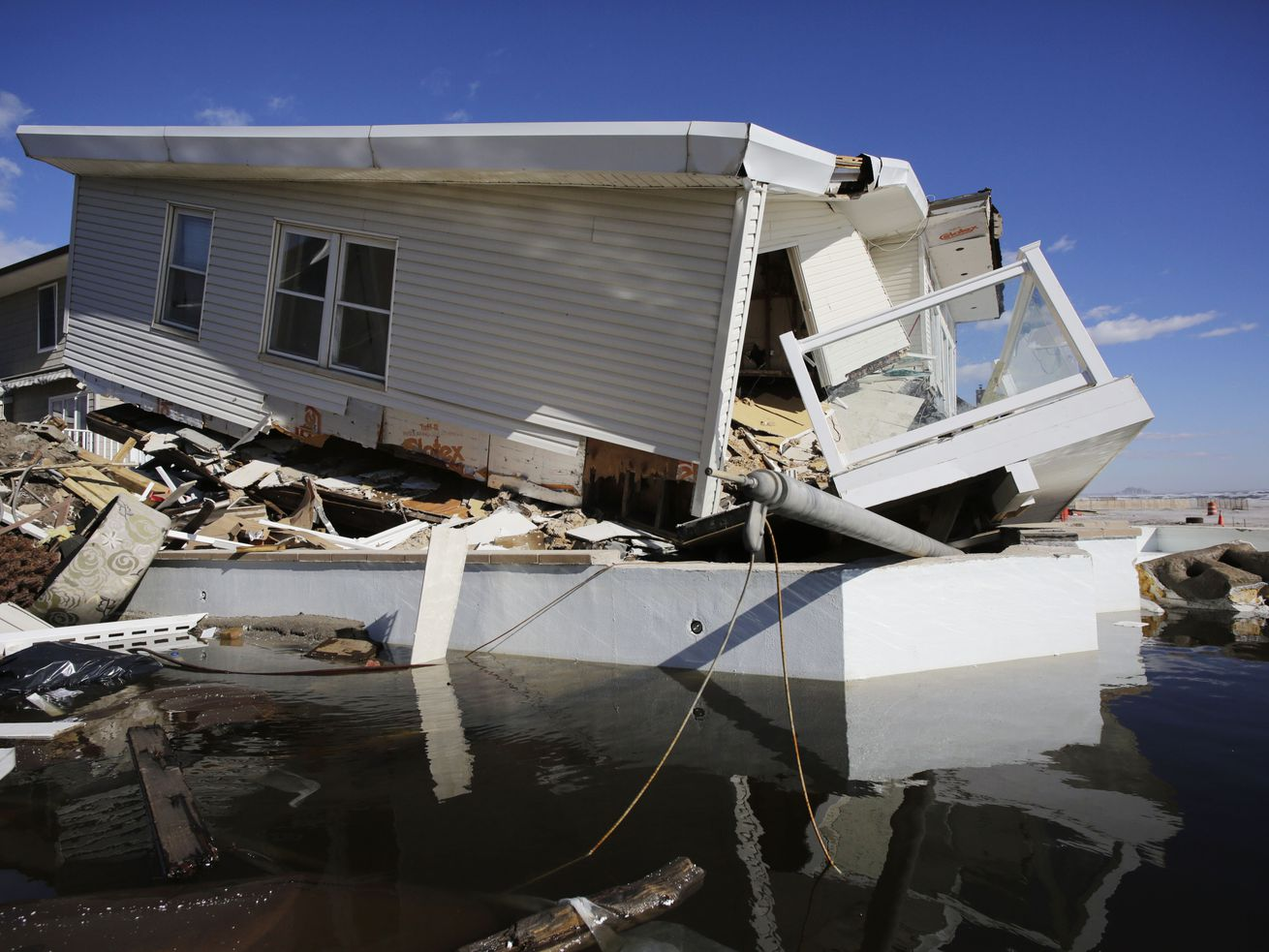 In this Thursday, Jan. 31, 2013 file photo, a storm-damaged beachfront house is reflected in a pool of water in the Far Rockaways, in the Queens borough of New York. A study released in the journal Nature Communications on Tuesday, May 18, 2021, says climate change added $8 billion to the massive costs of 2012's Superstorm Sandy.