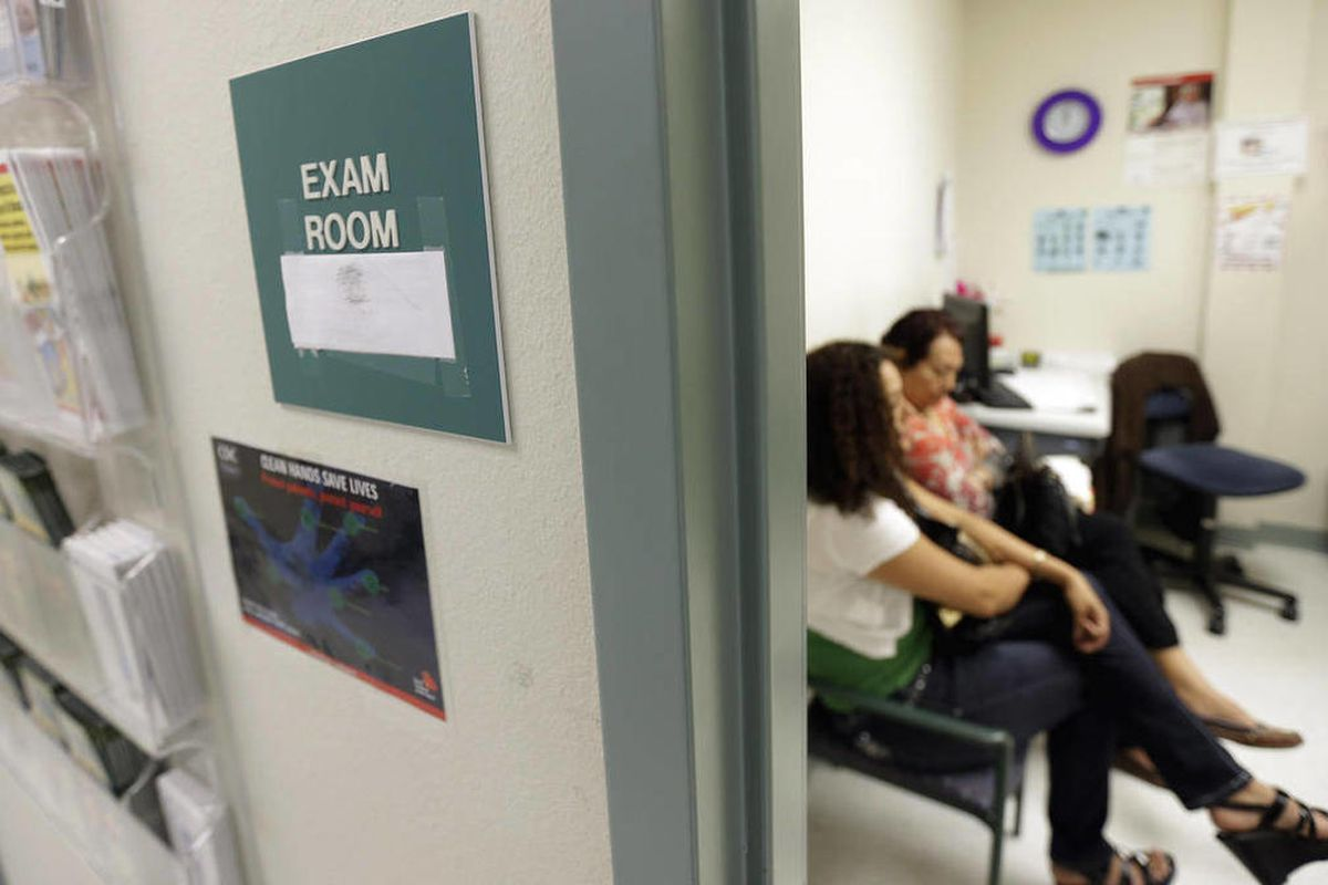 In this July 12, 2012 photo, two women wait in an exam room.