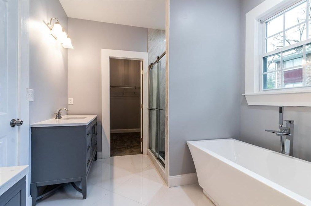 A gray master bathroom with a standalone white tub.