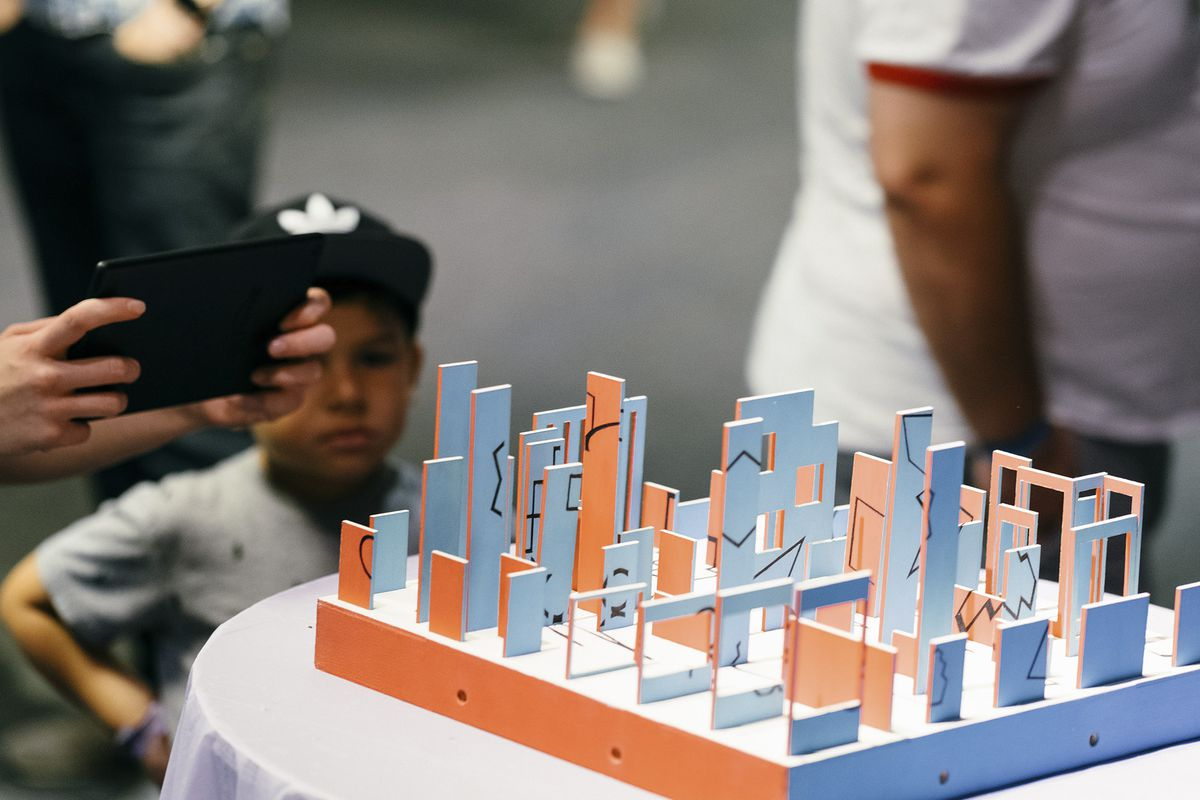 A person holding a tablet lines up a shot in GAZE. The game board is peach and light blue, with thing foam structures all over. Each one is inscribed with an obtuse black shape. Bit Bash at the Museum of Science and Industry in Chicago. 2019