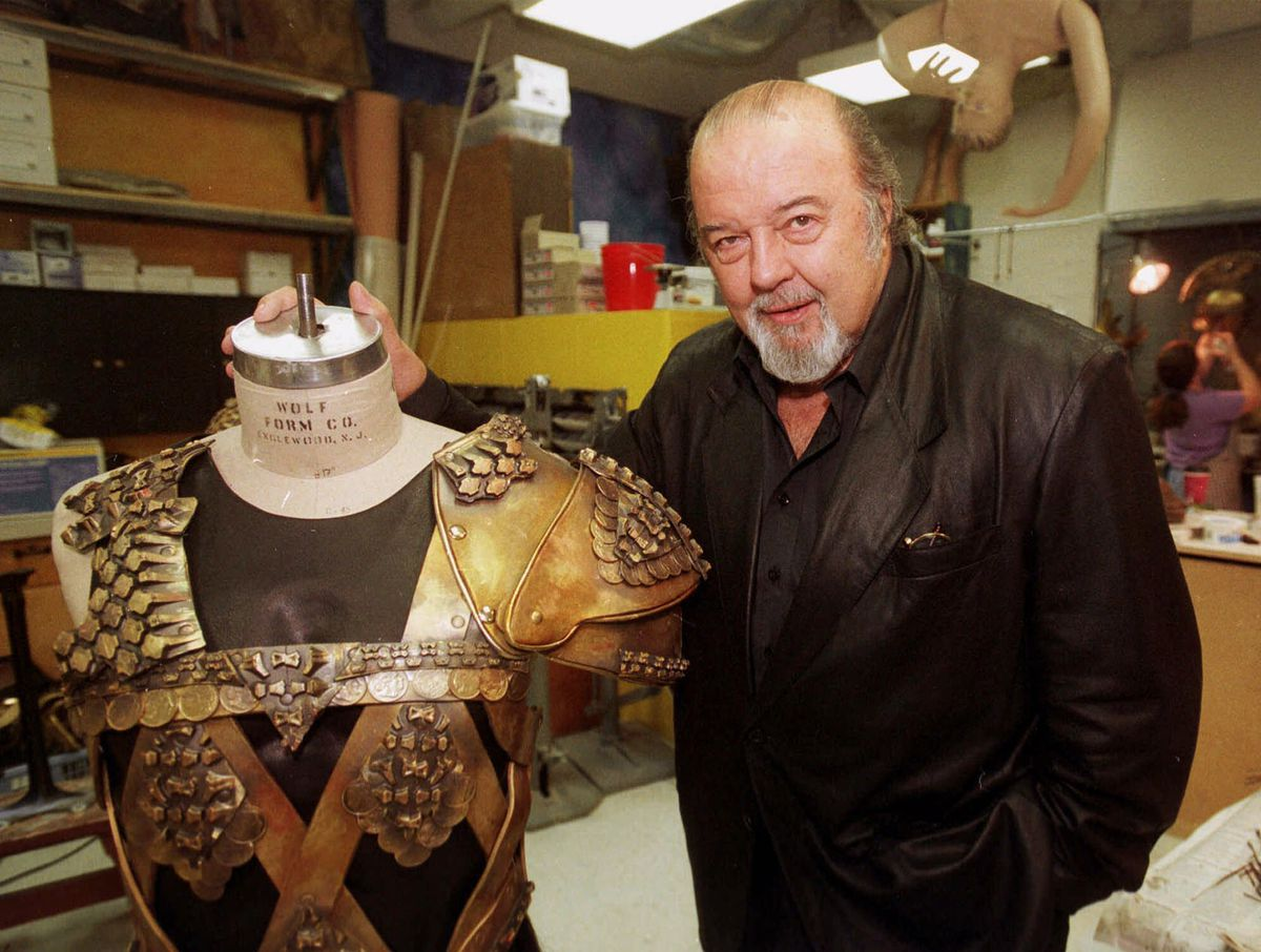 """Sir Peter Hall, director of the epic production, """"Tantalus,"""" poses with one of the suits of armor used in the 10 1/2-hour play at the Denver Center for the Performing Arts.   David Zalubowski/AP"""