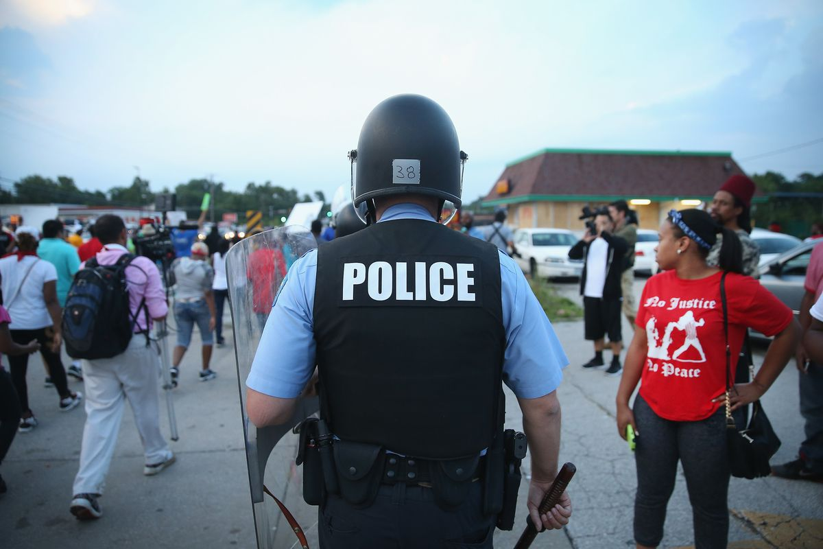 Police arrive in riot gear to enforce the first night of Ferguson's curfew.