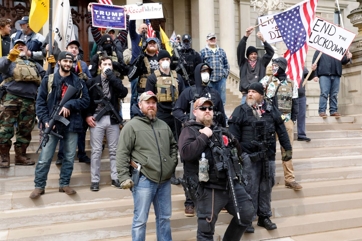 A small group of people stands on the steps of Michigan's state capitol, holding flags and signs, several armed with guns.