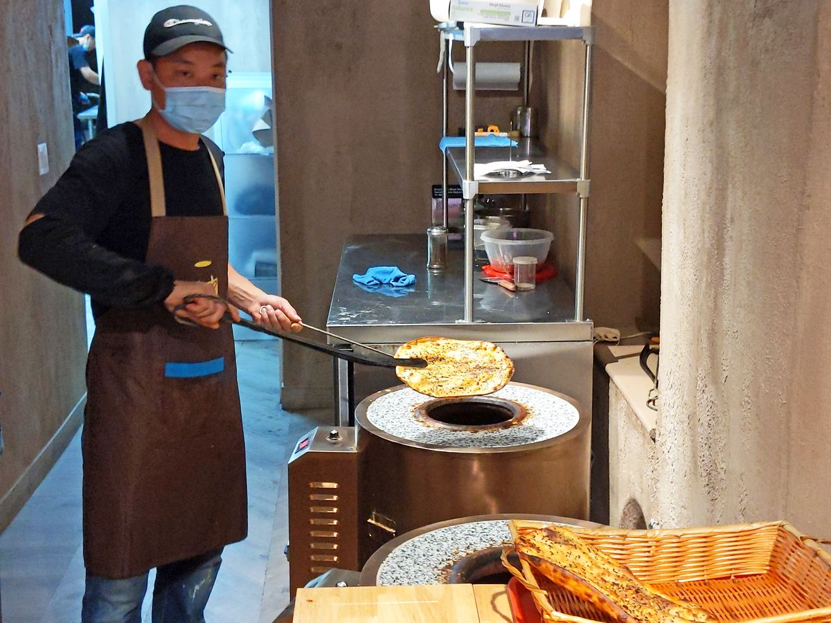 A cook in a mask stands before a vertical oven topped with tile and pulls out a flatbread with tongs.