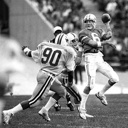 Brigham Young quarterback Robbie Bosco, right, tries to evade a pair of Wyoming tacklers during the 1984 season.