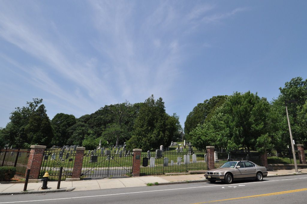 The view from across the street of a cemetery with a brick-and-iron fence around it.