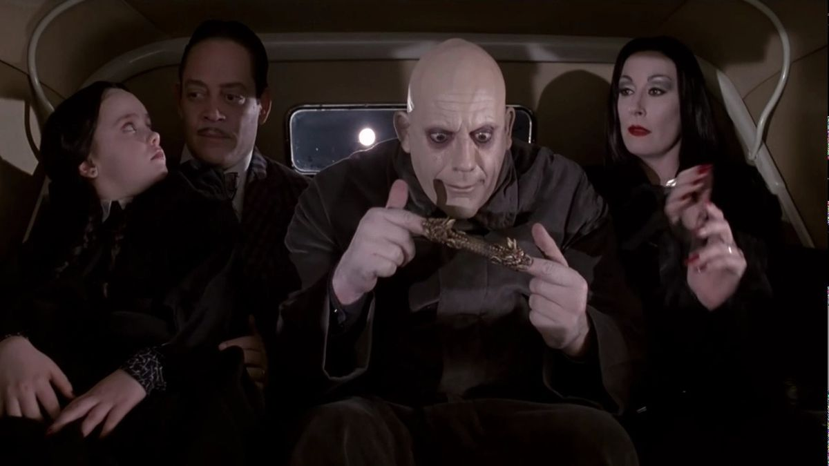 Wednesday Addams (Christina Ricci), Gomez Addams (Raul Julia), Uncle Fester (Christopher Lloyd), and Morticia Addams (Anjelica Huston) pile in the backseat of a car in The Addams Family (1991).