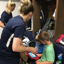 Amy Rodriguez helps her sons, Luke, left, and Ryan, right, find some entertainment on his tablet after Royals practice.