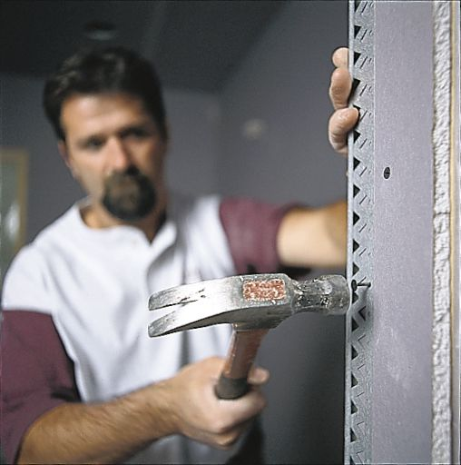Man Hammers Nail In Corners Of Drywall