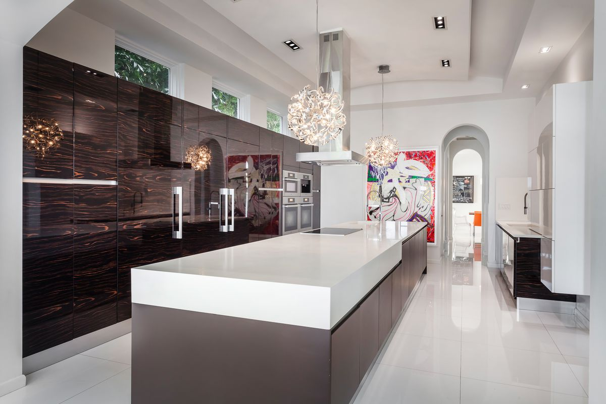 A modern kitchen in a Golden Beach mansion with white countertops and unique finishes.
