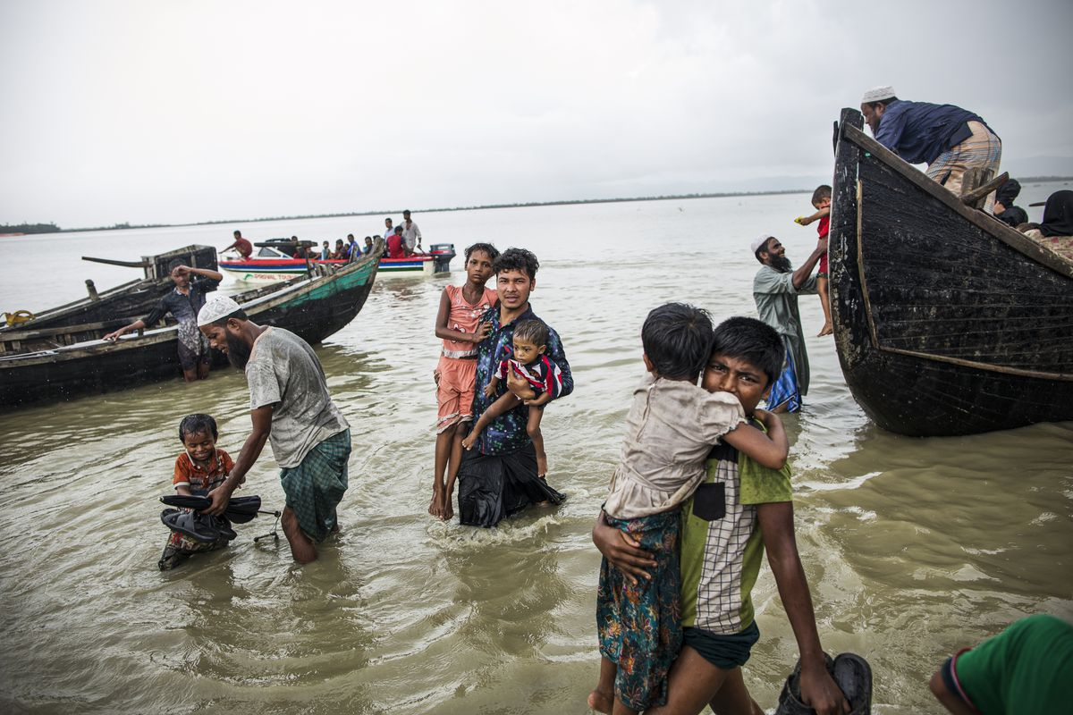 Refugees carry children ashore from wooden boats.