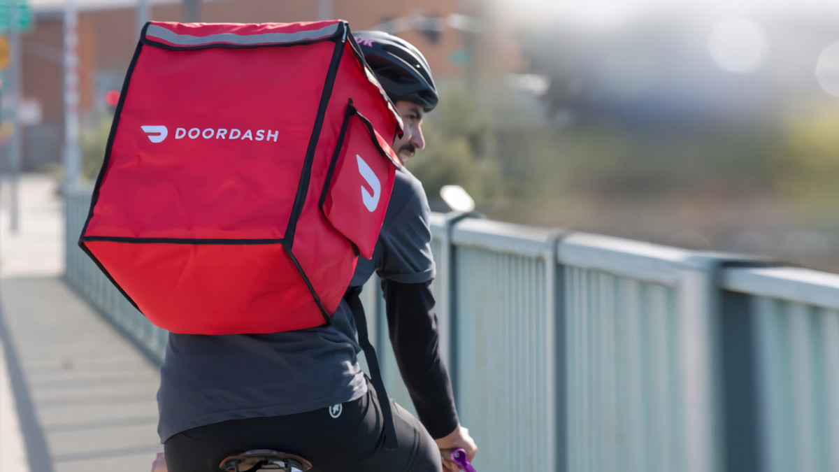 Man riding a bike with a DoorDash carrier strapped onto his back.