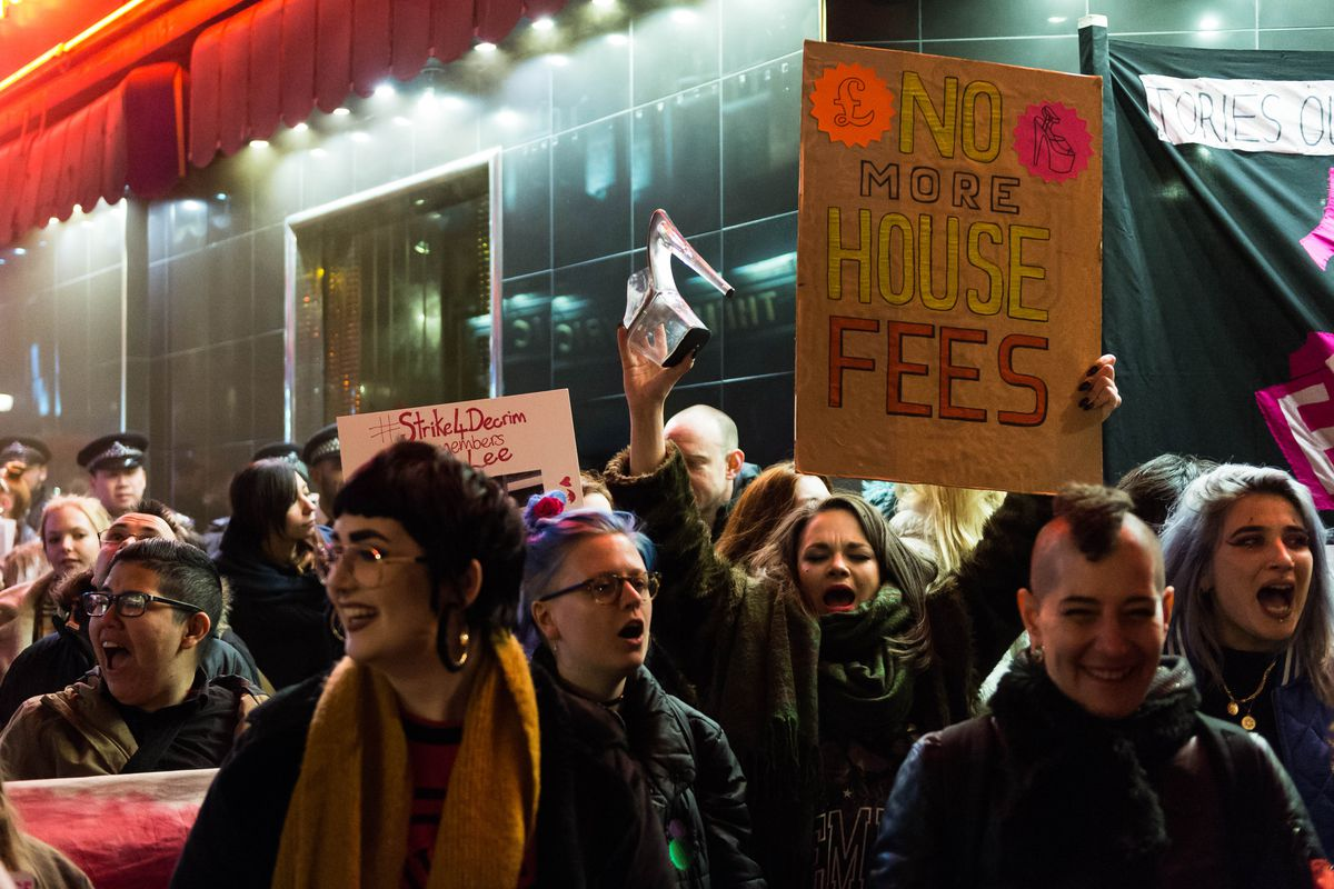 A woman holds a sign protesting the house fees that many strippers are  forced to pay to dance in clubs on International Women's Day on March 8,  2018, ...