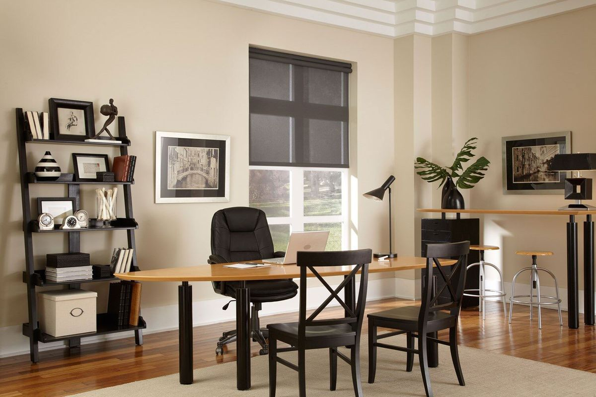 Office with a chair, table, and window with black screen.