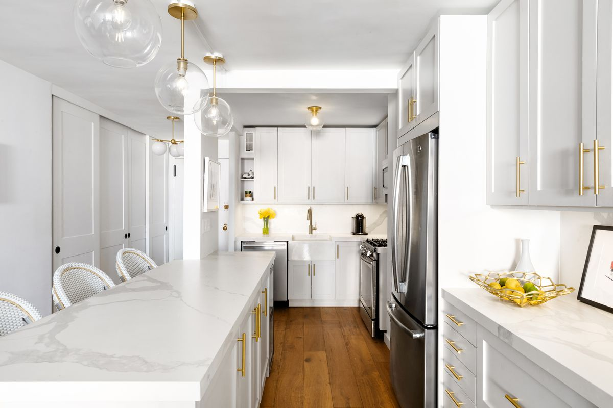 A kitchen with porcelain counters and golden drawer knobs.