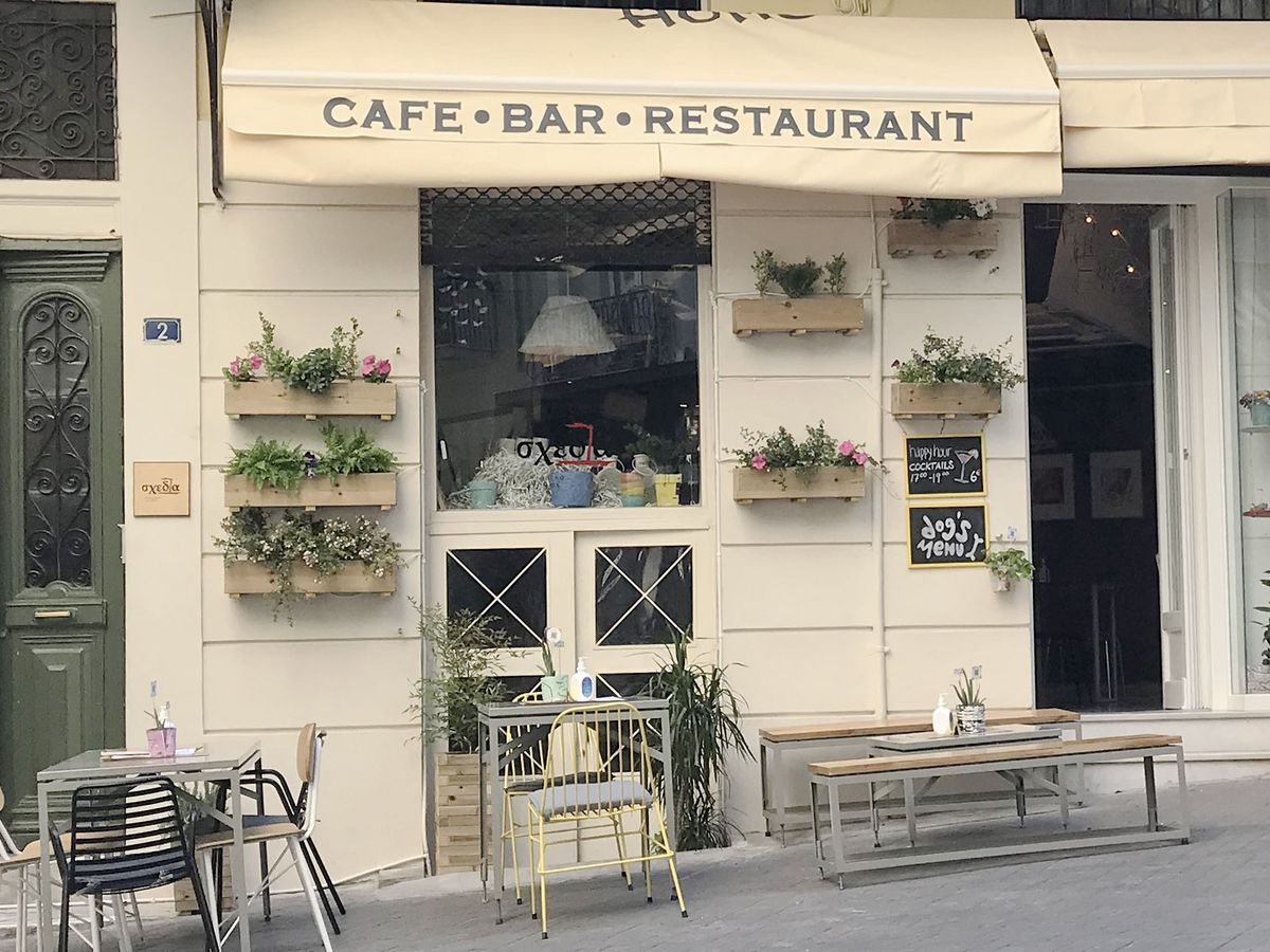 A restaurant exterior with branded awning, outdoor tables, planters, chalkboard signs, and street nearby