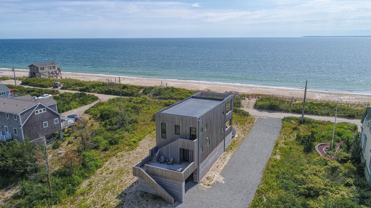 An aerial view of a contemporary, rectangular house in front of a sandy ocean beach.