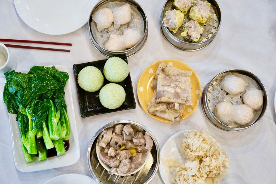 A white table at H.K. Cafe comes lined with greens, har gao, ribs in black bean sauce, and other dim sum classics.