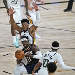 New Orleans Pelicans' Jrue Holiday (11) passes as Utah Jazz's Donovan Mitchell and Mike Conley (10) defend during the second half of an NBA basketball game Thursday, July 30, 2020, in Lake Buena Vista, Fla. (AP Photo/Ashley Landis, Pool)