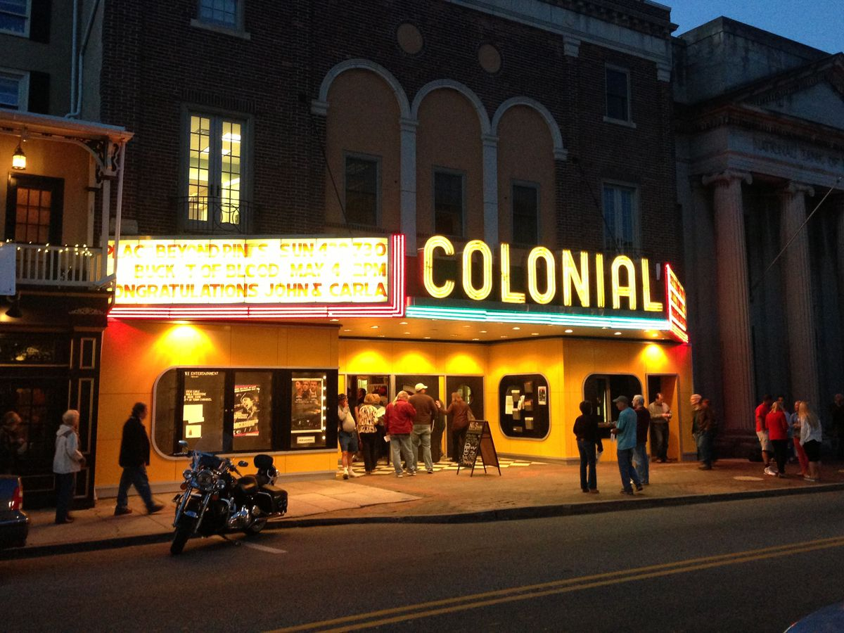A street in Phoenixville, Pennsylvania. There is a movie theater that has a neon sign that reads: Colonial.