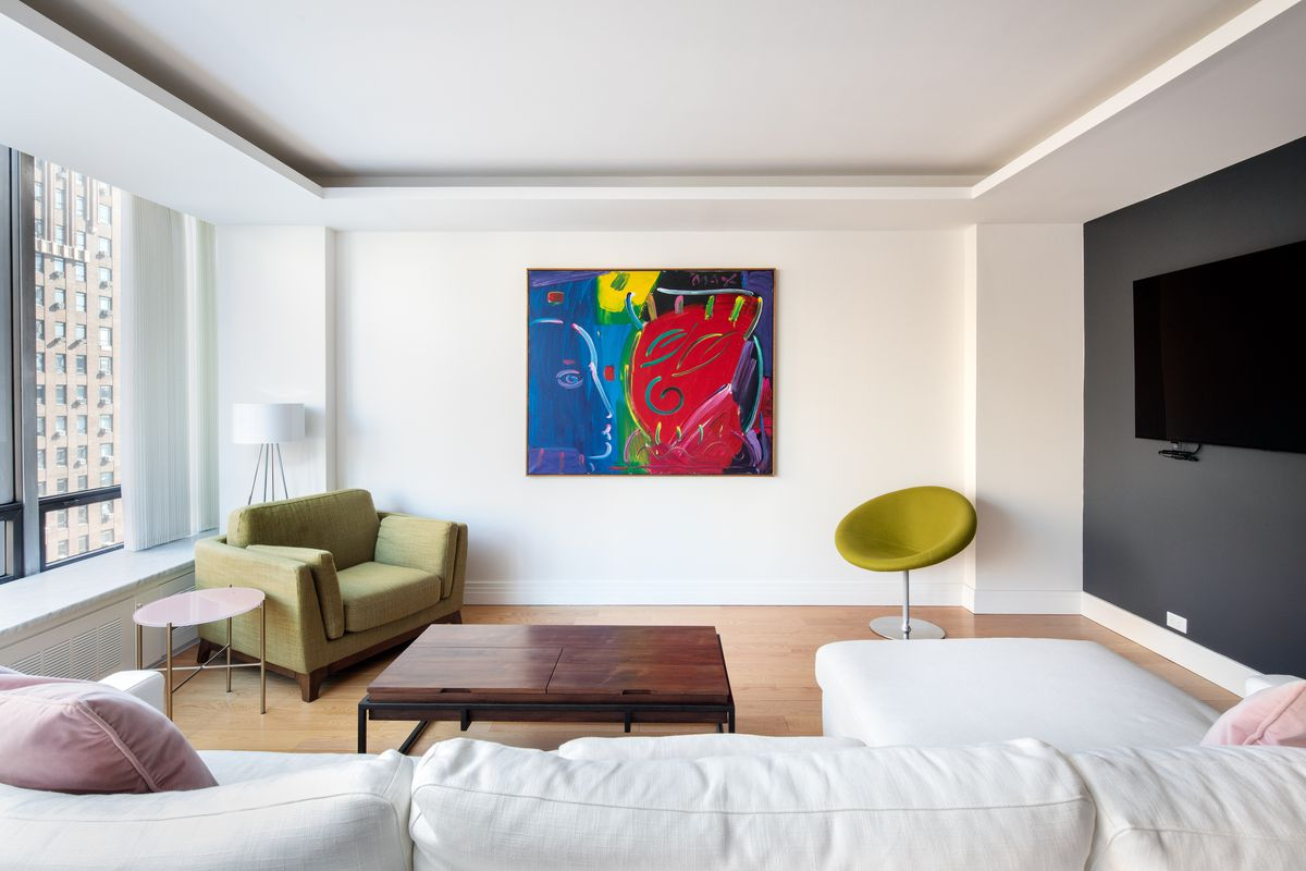 A living room with large windows, a TV on the wall, a white couch, a colorful painting, and two green chairs.