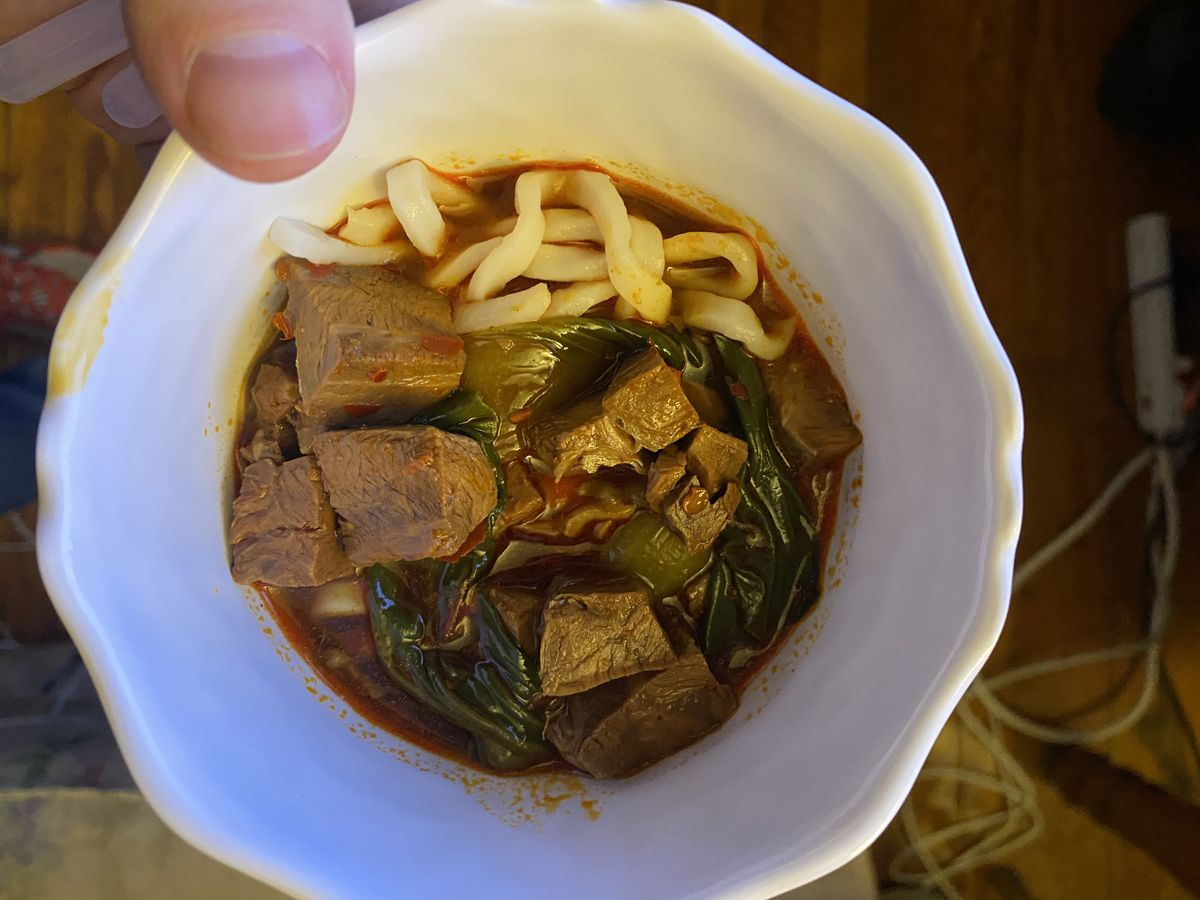 Cubes of beef and white noodles sit atop a reddish broth in a white bowl