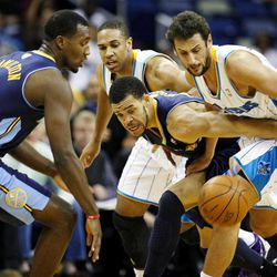 New Orleans Hornets guard Marco Belinelli (8) scrambles for a loose ball with Denver Nuggets center JaVale McGee (34) during the first half of an NBA basketball game, Wednesday, April 4, 2012, in New Orleans.