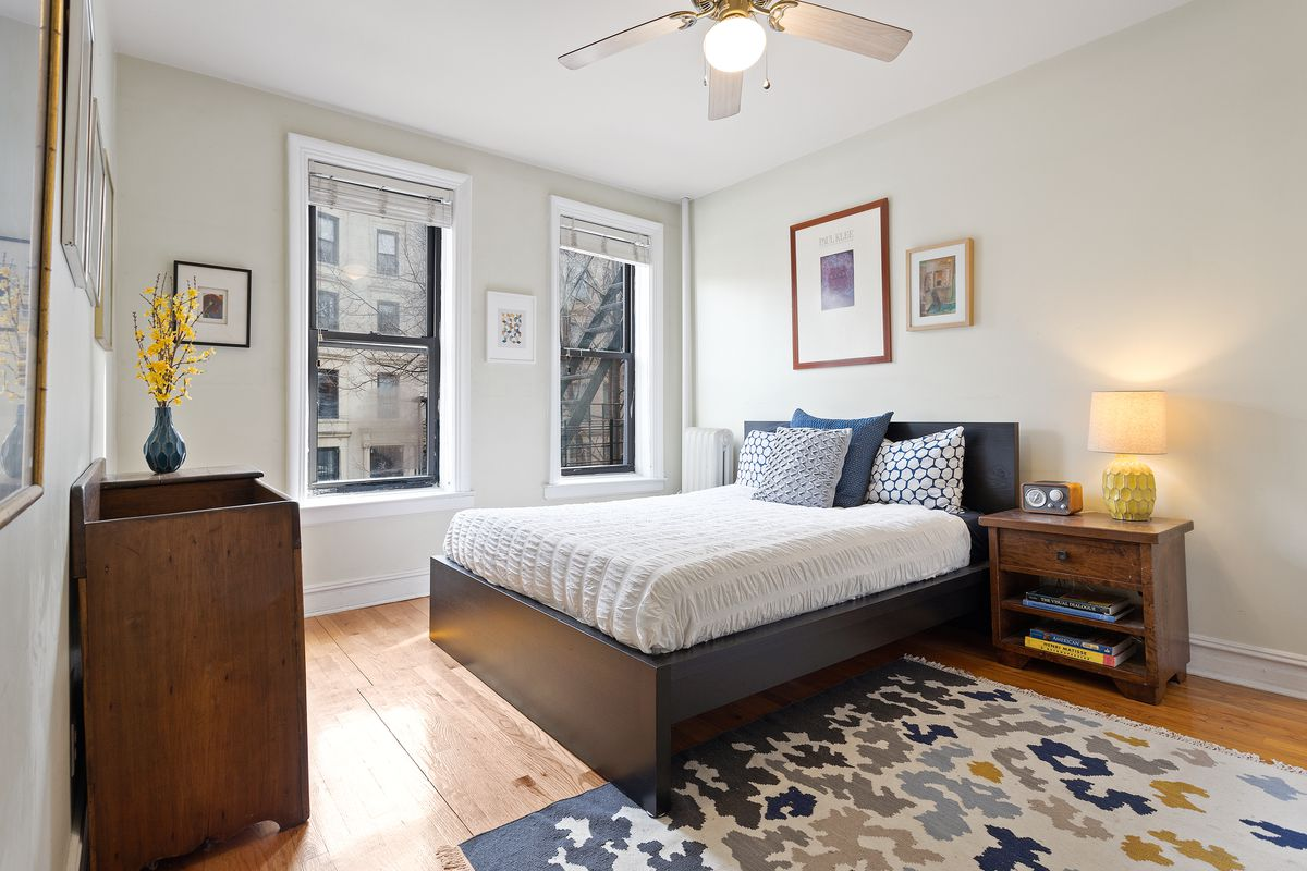 A cream-colored bedroom with two windows, wood floors, and baseboards has a queen sized bed.