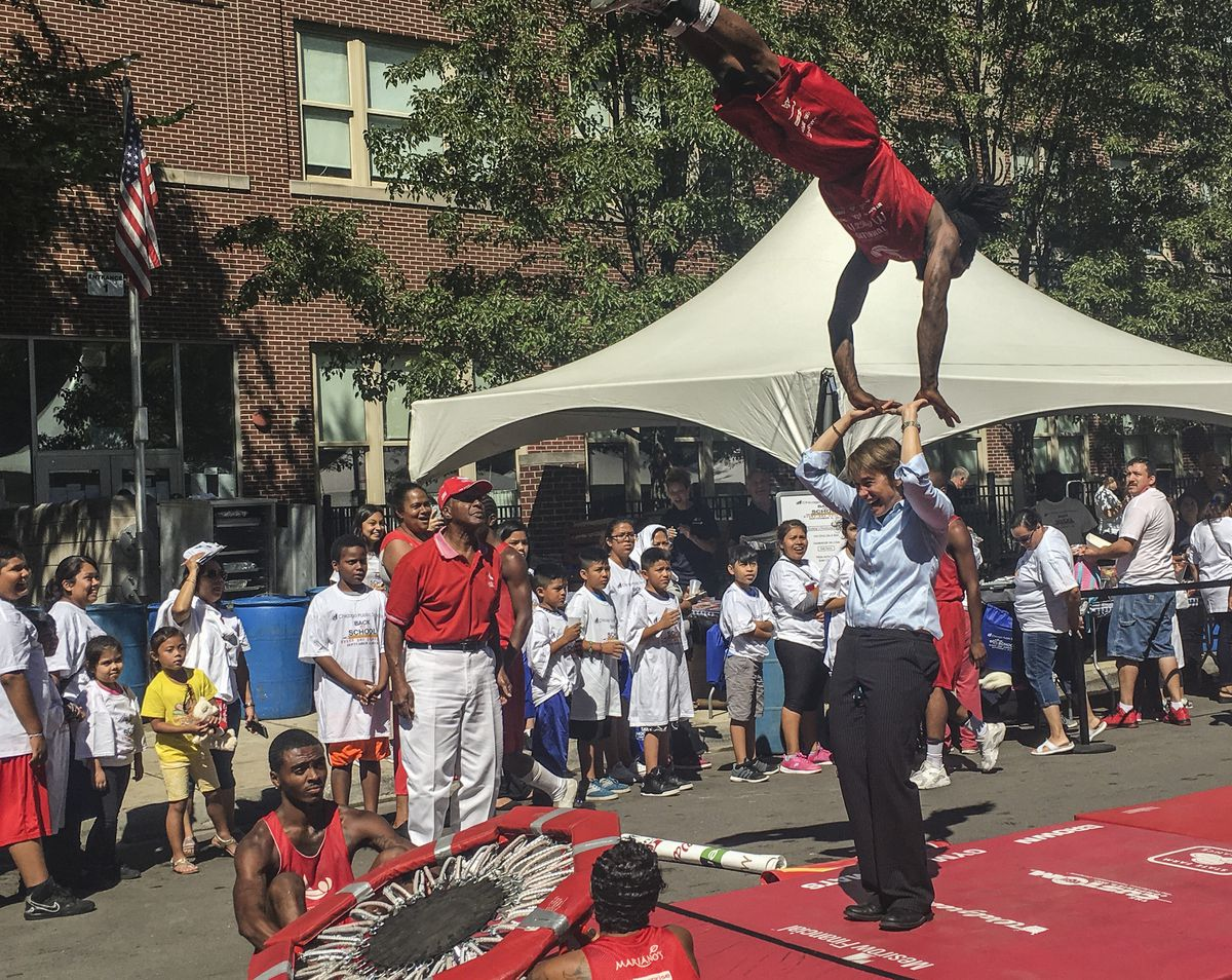 Secretary of State Jesse White (red cap) watches members of his Tumbling Team at a CPS back-to-school party in 2016.