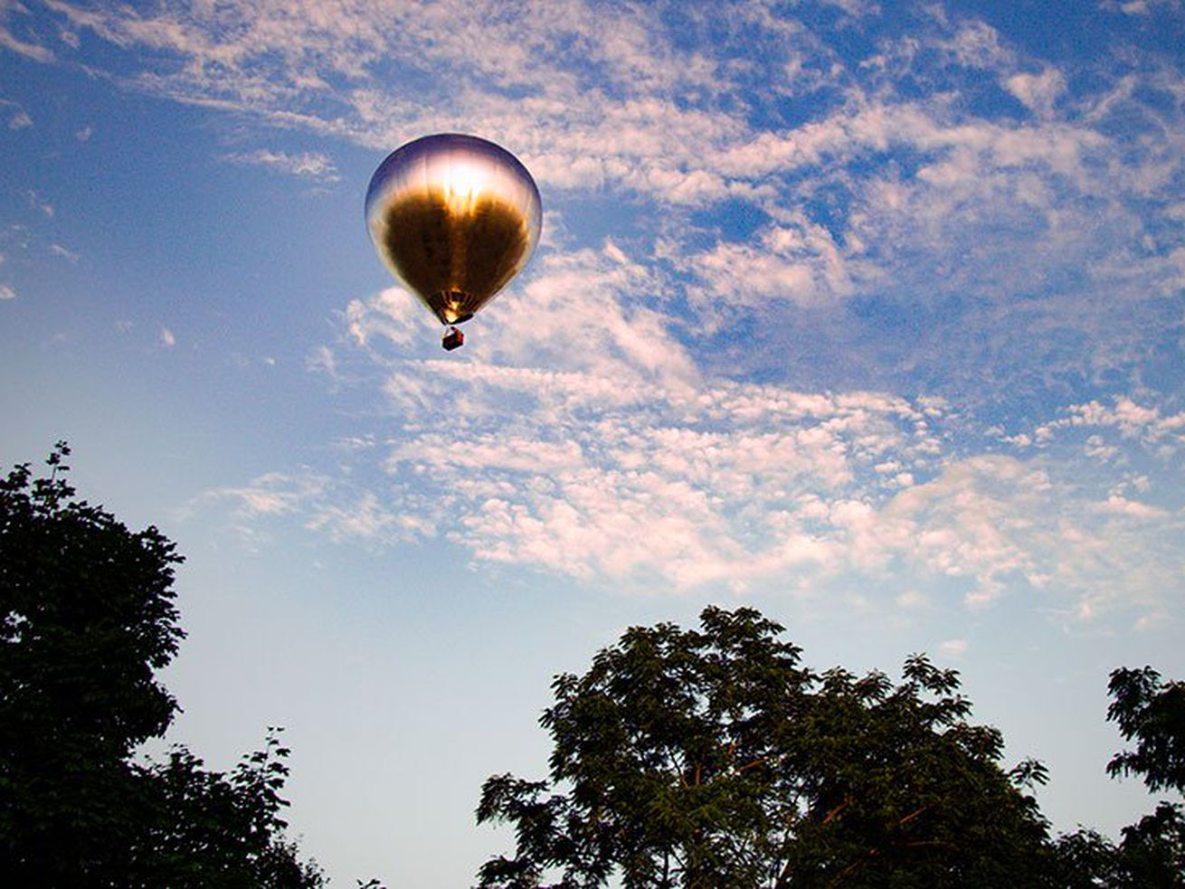 mirrored hot air balloon flying over the landscape