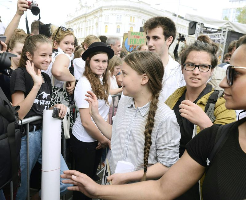 Climate activist Greta Thunberg waves to a supporter in a crowd held back behind a barricade.