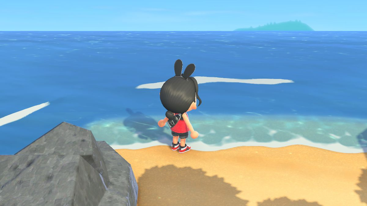 An Animal Crossing character stands on the small, secret beach area, facing the ocean