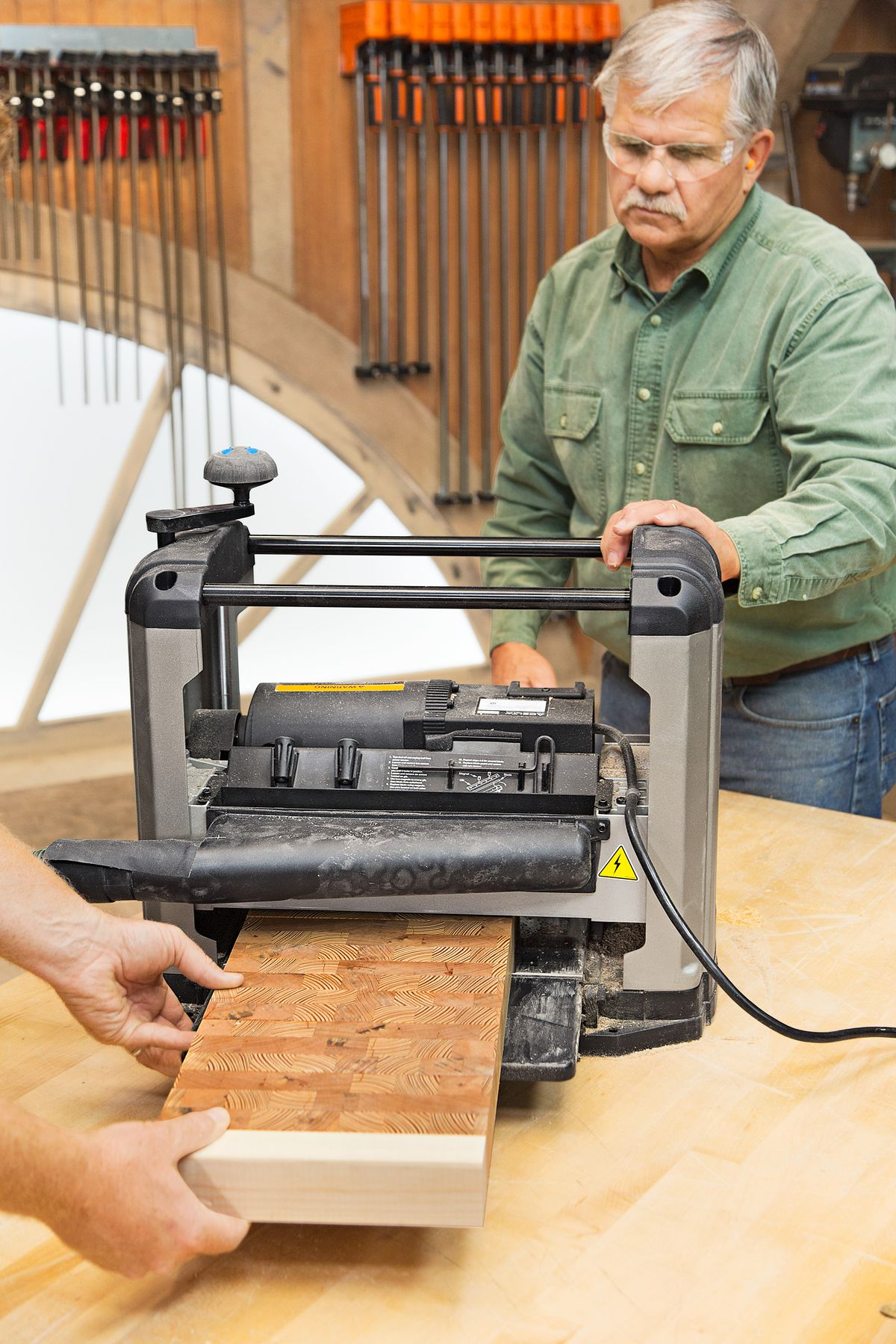 Person using a thickness planer to smooth the face of the end grain cutting board.