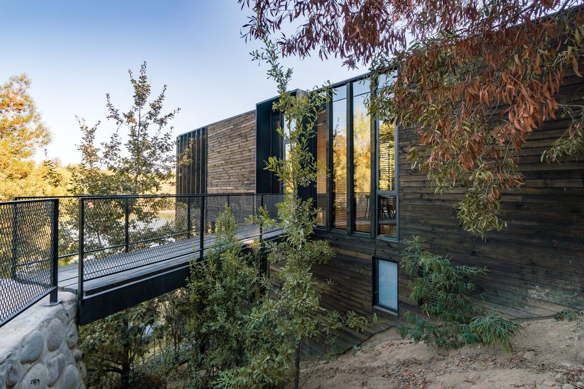 A frame with wired railing leads to a boxy house made of timber, glass, and steel.