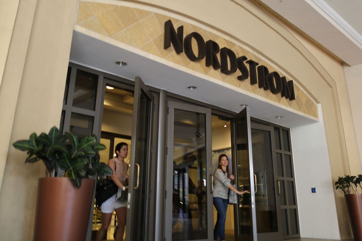 The front entrance of a Nordstrom's department store with women exiting through the glass doors