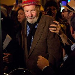 """Activist musician Pete Seeger, 92, exits the Symphony Space on the Upper West Side to march with nearly a thousand demonstrators sympathetic to the Occupy Wall Street protests for a brief acoustic concert in Columbus Circle, Friday, Oct. 21, 2011, in New York. The demonstrators marched down Broadway singing """"This Little Light of Mine"""" and other folk and gospel songs while ad-libbing lines about corporate greed and social justice."""