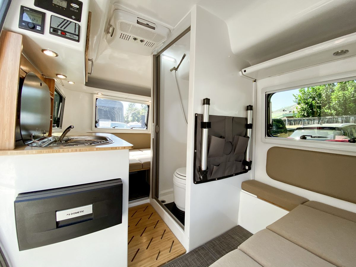 The interior of the camper has a small sink and kitchenette, large windows, and a bathroom with shower in between the two sleeping spaces.