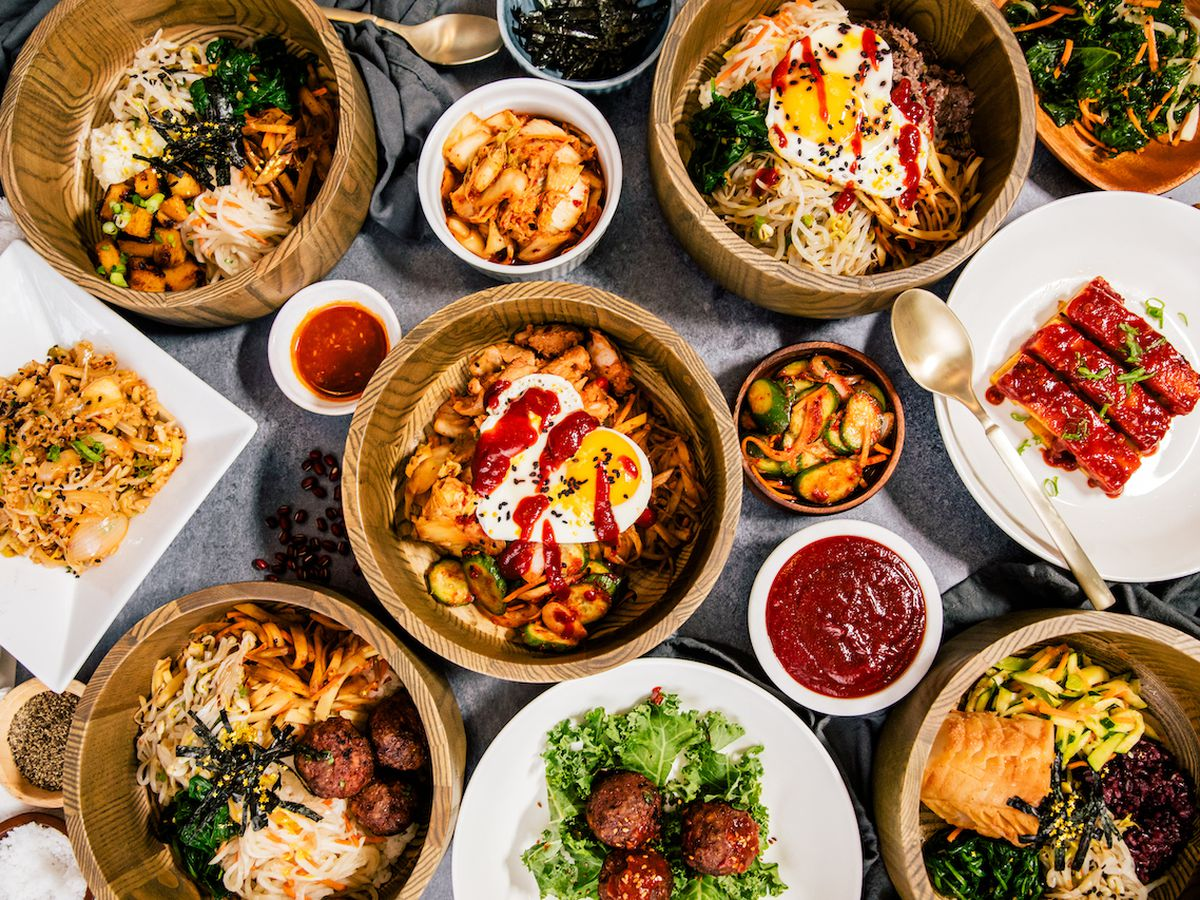 a variety of bowls filled with colorful Korean food on top of griddle