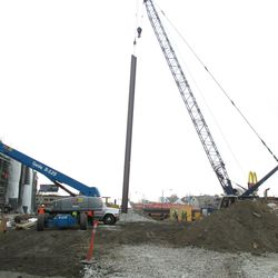 Beam being lifted in the triangle lot. As I was leaving, this beam was lowered back down.