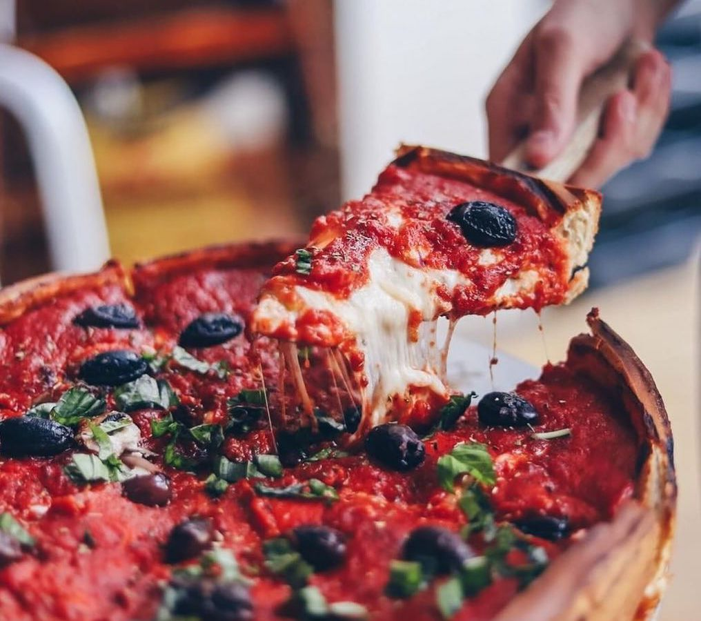 Patxi's deep dish pizza being pulled out of its tray.
