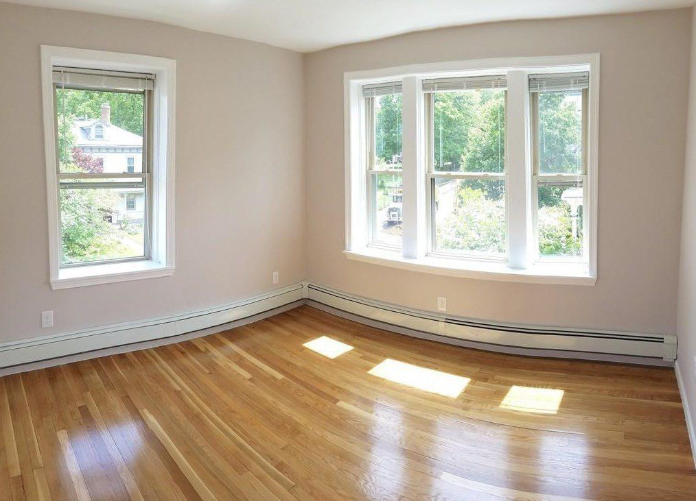 An empty corner bedroom with two windows.
