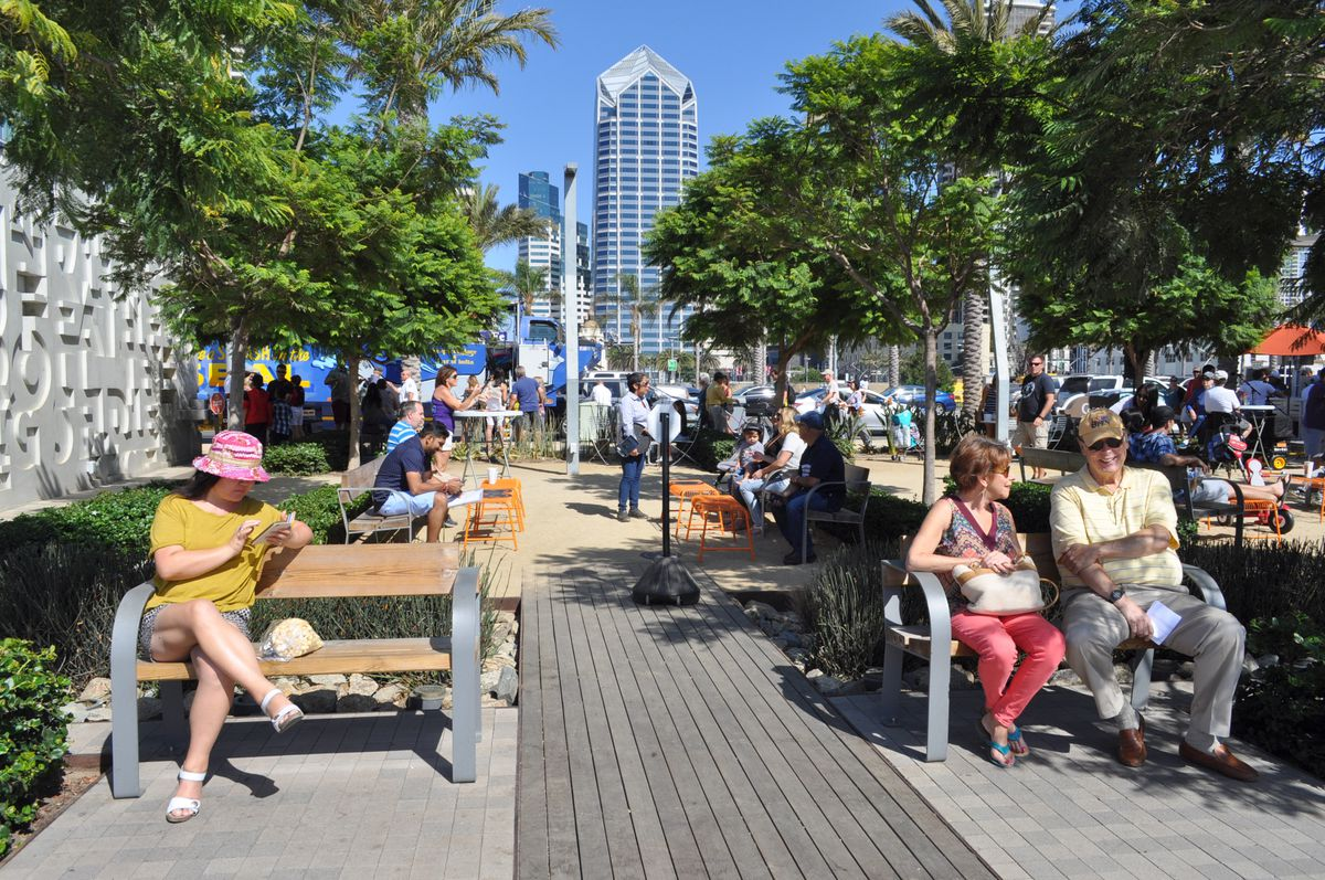 People sit on benches in a park by the water, with many trees for shade and a view of downtown buildings.