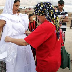 A Yezidi woman in Bajed Kandala 2, a camp near the borders of Syria and Turkey housing internally displaced people, receives a new dress from Doctor Nemam Ghafouri. LDS Charities is working with other humanitarian organizations to provide the Yezidi women with white dresses, which are a symbol of their religious identity.