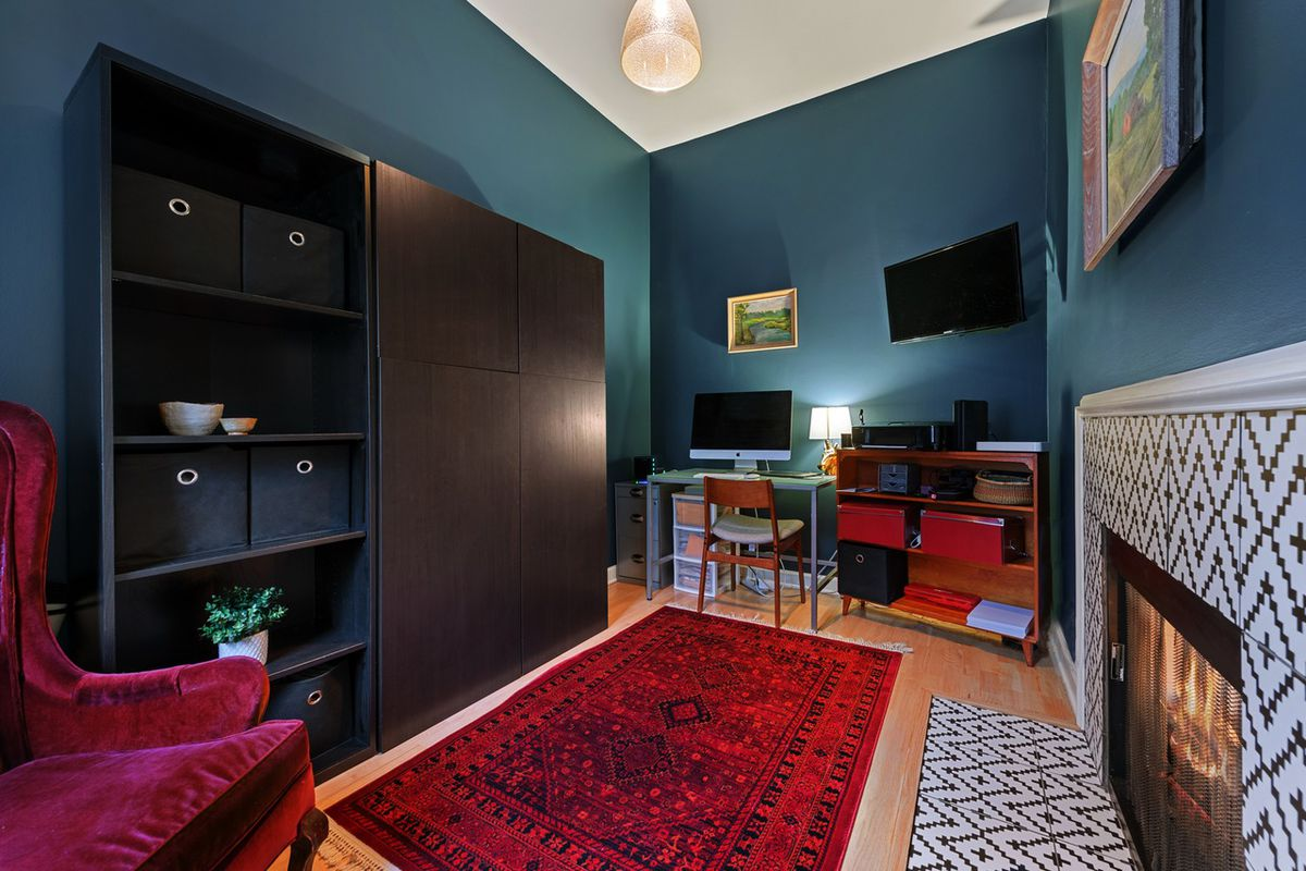 A study with green walls, storage shelves, and a fireplace lined with a tile pattern.
