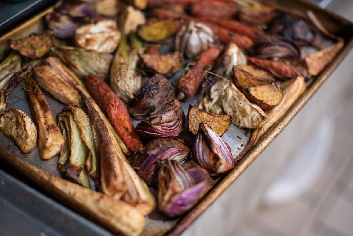 Slow-roasted vegetables on a sheet tray before dinner service at a restaurant.