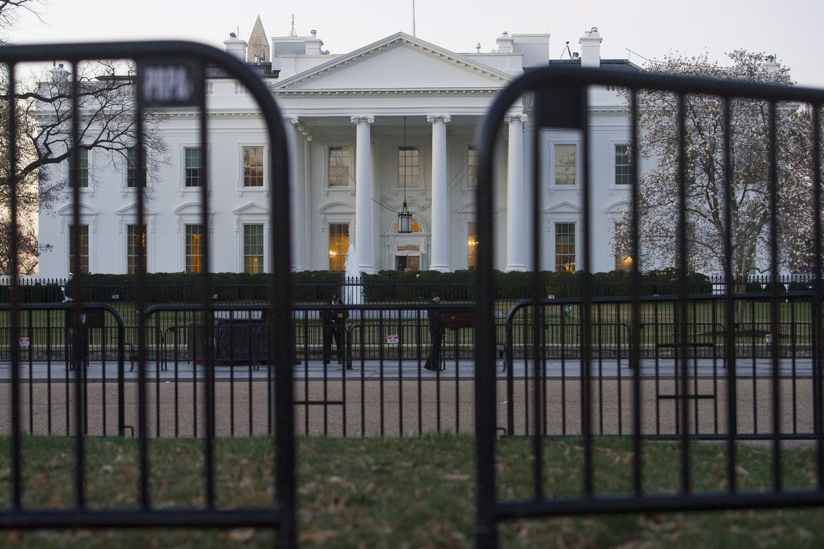 In this March 24, 2019 photo, the White House is seen behind security barriers in Washington. A White House official turned whistleblower says dozens of people in President Donald Trump's administration were granted access to classified information despit
