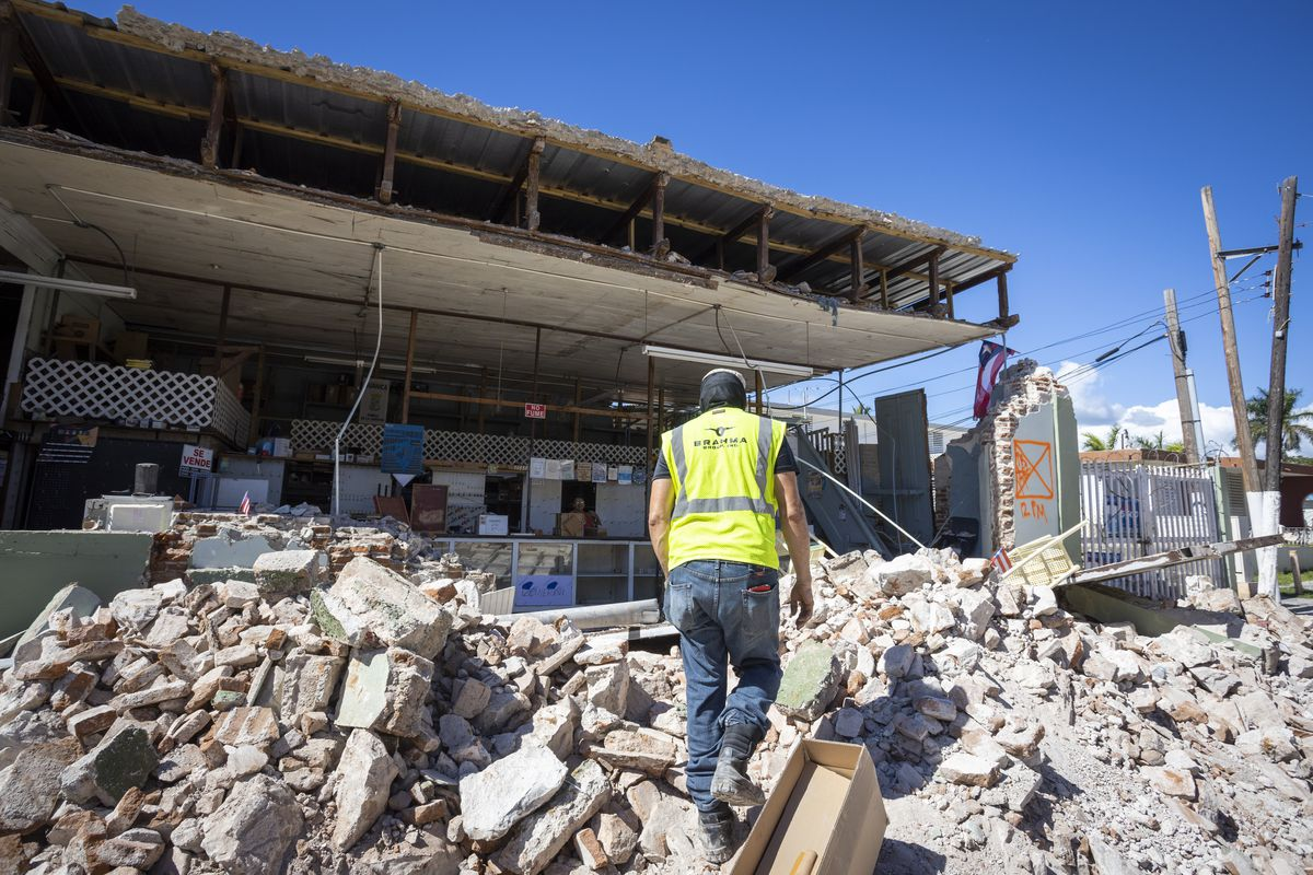 Wearing a neon yellow vest, a man carefully steps through debris, approaching the remains of a building whose walls have tumbled.