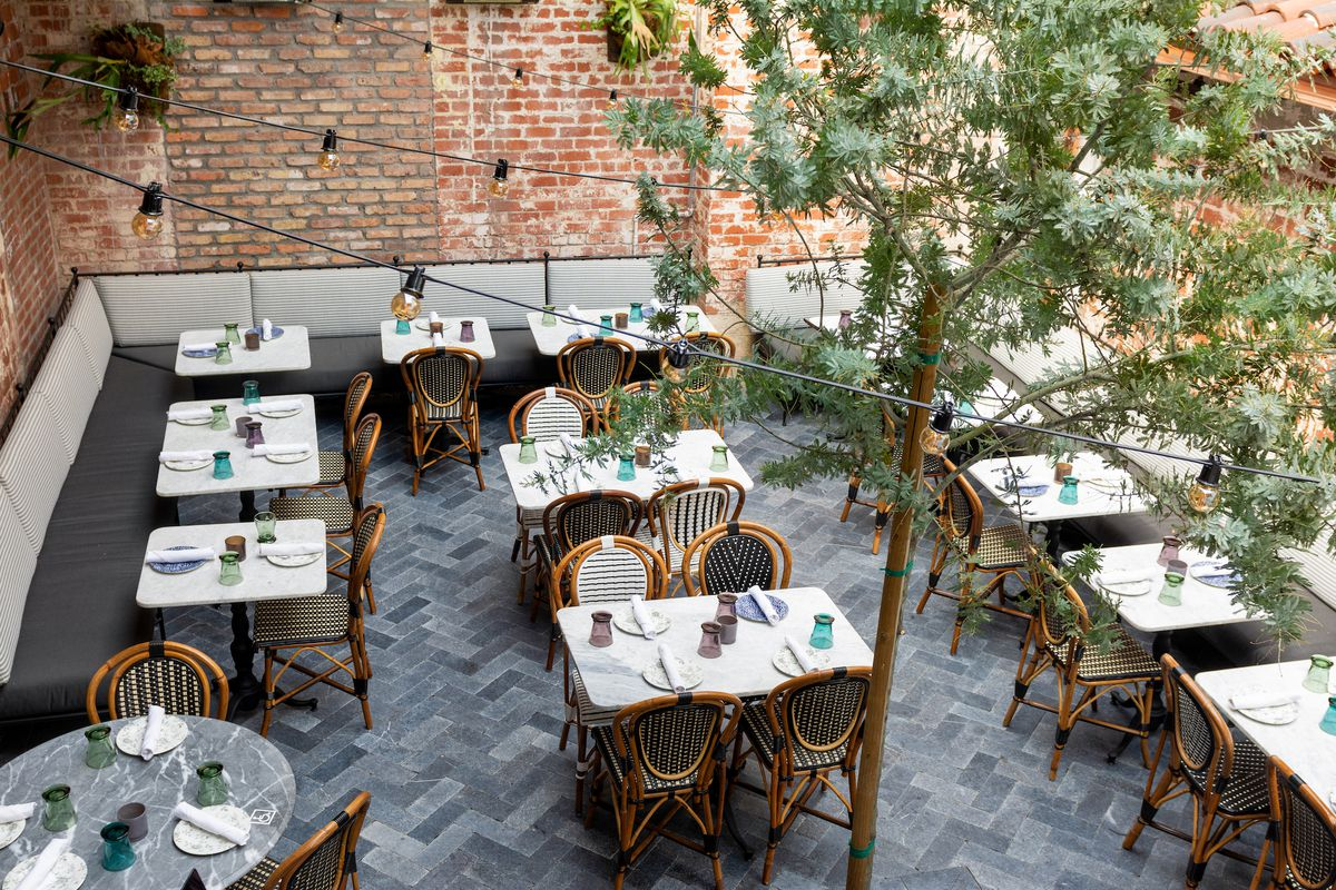 A French bistro patio with herringbone tile and greenery.
