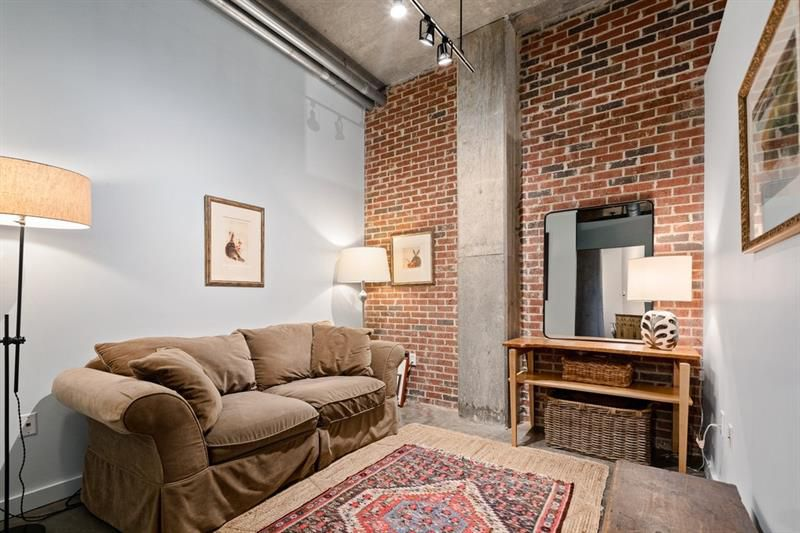 A couch a left in a small room with a tall brick wall.